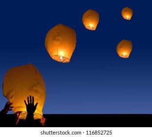 yellow lantern in human hands on dark background
