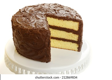 Yellow layer cake with chocolate icing with one slice missing.