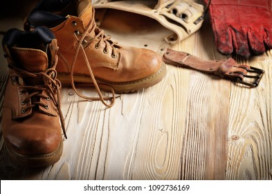 Yellow leather used work boots with tool belt and protective gloves on wooden background closeup. Place for text