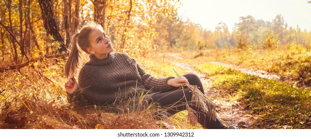 Yellow leaves above the lake. Autumn landscape. Young tourist woman on the beach in the crystal clear water, tourism, travel,hugge,lagom. Long banner