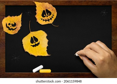 Yellow leaves with Halloween faces on the chalkboard, the girl's hand writes in white chalk. Copy space for text. Flat lay