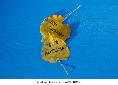 Yellow leaves with an inscription HELLO AUTUMN and BYE SUMMER on a wooden blue background
