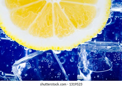 Yellow lemon in the glass of cold sparkling water and ice.