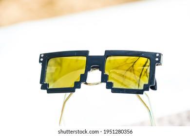 Yellow lenses pixel 8bit sunglasses design shoot in a summer day closeup.  Selective focus