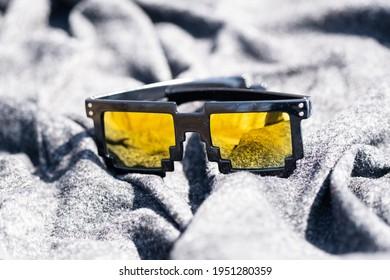 Yellow lenses pixel 8bit sunglasses design shoot in a summer day closeup.Thug life model. Selective focus
