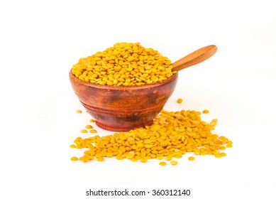 Yellow lentils in a wooden bowl with spoon overflowing, against white background