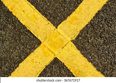 Yellow letter X painted on the asphalt