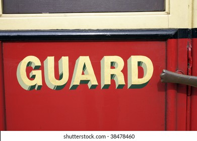 Yellow lettered sign saying 'guard' against a red painted steam train