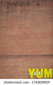 """Yellow Lettering saying """"YUM"""" with red Brick Wall in Backgrround"""