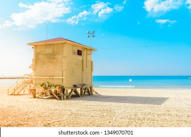 Yellow lifeguard tower at sandy Tel Aviv Beach, Israel, against blue horizon. Summer, baywatch, vacation and travel concept.