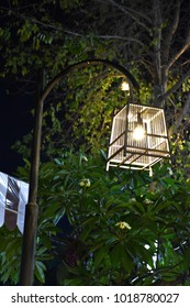 Yellow light bulb in a bamboo cage at night in the garden.
