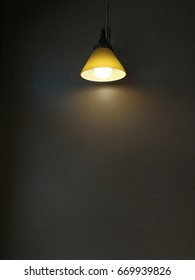 Yellow light bulb hang in the room on gray wall background. Interior design by a little decoration, The light bulb is a good choice to decorate your room