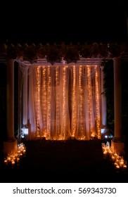 Yellow light garlands hang from wedding altar made of pillars
