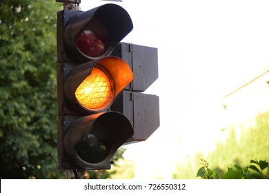 Yellow light of traffic lights in summer city
