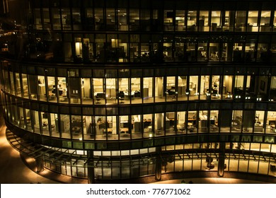 yellow light windows of an office building at night in Boston late night at work. glass curtain wall office building