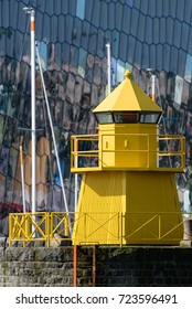 Yellow lighthouse in the Reykjavik, Iceland harbor with abstract glass exterior of the Harpa concert on the background with reflections in the windows and masts of the sailing boats in between.