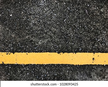 Yellow line with asphalt road texture background.