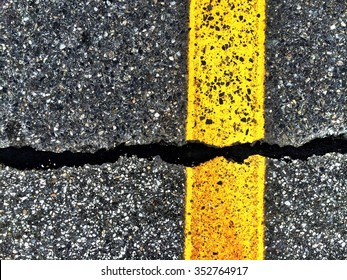 Yellow line and black tar on pavement, with texture and strong geometry