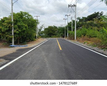 The yellow line divides the lane on the road. The cement road has a yellow lane dividing line to reduce accidents. The structure of the road made of cement.