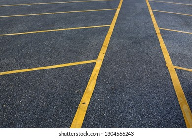 yellow line marking parking lots on black asphalt road surface texture