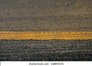 yellow line on asphalt road crack surface