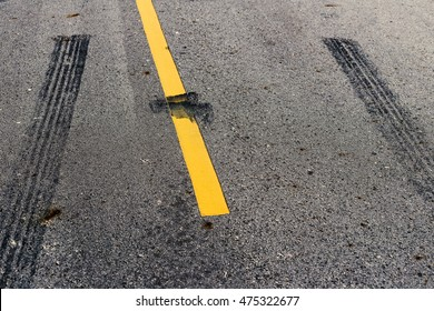 Yellow line on the high way. Conceptual of accident between tire track.