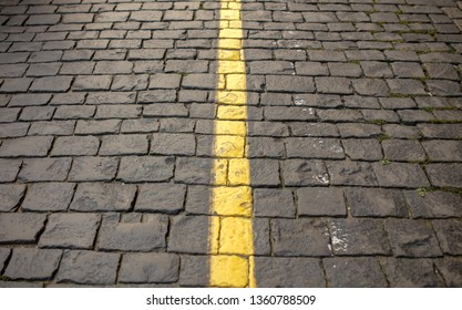 Yellow line on paving stone as abstract background .