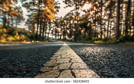 Yellow line rough surface and grey cracked asphalt road texture in vintage style.