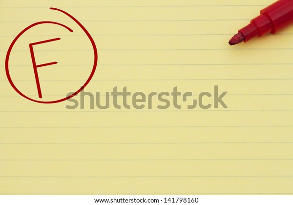 Yellow Lined Paper with the grade F in red circled and a marker, Getting a bad grade
