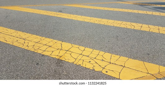 yellow lines with cracks on black asphalt