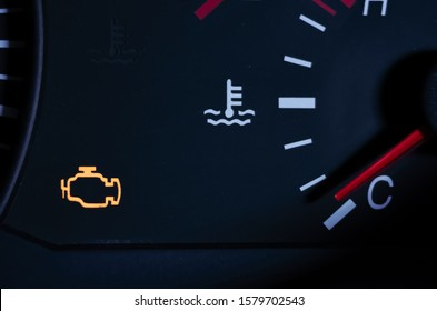 Yellow lit engine error sign on car dashboard close up