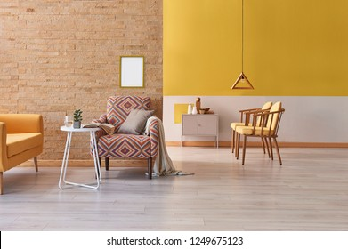 Yellow living room, yellow chair and sofa furniture decoration, home design, brick wall background with frame on the wall.