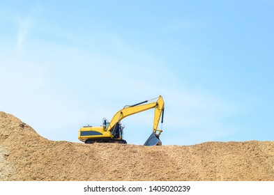 Yellow loader backhoe on pile dry wood chips with blue sky. Industrial in factory.