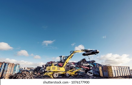 Yellow loader crane machine loading car on metal scrap yard