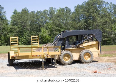A yellow loader in a lot with a trailer