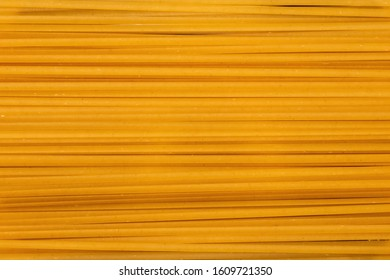 Yellow long spaghetti background, thin uncooked pasta arranged in rows, raw spaghetti wallpaper with copy space and food concept
