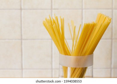 Yellow long spaghetti in a glass jar on the background of the kitchen. Yellow Italian pasta. Long spaghetti. Raw spaghetti. The concept of food. Concept of Italian cuisine and menu.