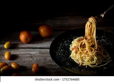 Yellow long spaghetti. Yellow italian pasta. Long spaghetti. Raw spaghetti. Italian food. The fork is scooping the spaghetti.
