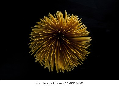 Yellow long spaghetti on a black background. Yellow Italian pasta. Long spaghetti. Raw spaghetti bolognese. Raw spaghetti. Food concept background. Italian food and menu concept.
