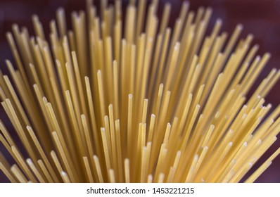 Yellow long spaghetti on a rustic background. Yellow italian pasta. Long spaghetti. Raw spaghetti bolognese. Raw spaghetti. Food background concept. Italian food and menu concept.
