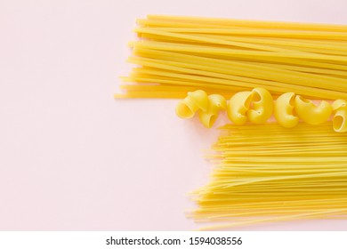 Yellow long spaghetti on a rustic background. Yellow Italian pasta. Long spaghetti. Raw spaghetti Bolognese. Raw spaghetti. The concept of food. Concept of Italian cuisine and menu. Flat lay.