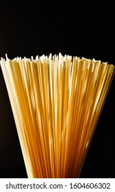 Yellow long spaghetti on shining black background. Thin pasta arranged in rows. Yellow italian pasta. Long spaghetti. Raw spaghetti bolognese. Raw spaghetti wallpaper. Food background concept.