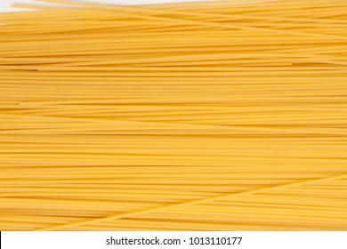 Yellow long spaghetti . Thin pasta arranged in rows. Yellow italian pasta. Long spaghetti. Raw spaghetti wallpaper. Thin spaghetti. Food background concept.