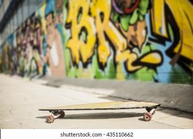 yellow longboard near the concrete grafiti  wall in perspective. no people.