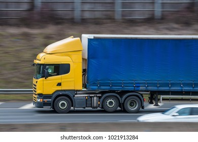 Yellow lorry with blue trailer in motion on the motorway