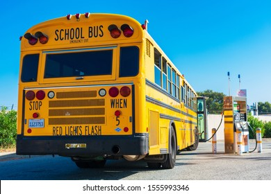 Yellow low emissions school bus refuel cleanest burning alternative fuel at compressed natural gas CNG fueling station owned by PG&E - San Carlos,  CA, USA - 2019