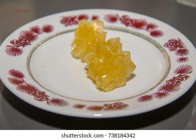 Yellow lump sugar on the dish. Natural product.