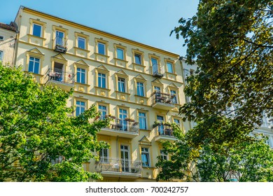 yellow luxury facade with green trees