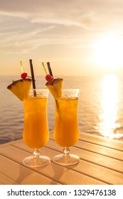 Yellow luxury summer sun cocktail at tourism sea sunset paradise. Fresh cool juicy orange pineapple coktails. Perfect wellness drink for enjoyment and relaxation at holiday cruise or vacation travel