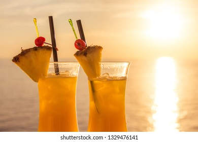 Yellow luxury summer sun cocktail at sea sunset tourism paradise. Fresh cool juicy orange pineapple coktails. Perfect wellness drink for enjoyment and relaxation at holiday cruise or vacation travel